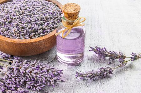 Glass bottle of Lavender essential oil with fresh lavender flowers on white wooden rustic table, aromatherapy spa massage concept. Lavendula oleum Imagens