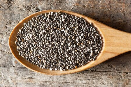 Chia seeds (Salvia Hispanica) in wooden spoon. Cereal healthy food contains omega 3, a dietary supplement gluten free