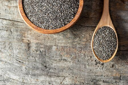 Chia seeds (Salvia Hispanica) in wooden spoon and bowl on wooden background. Cereal healthy food contains omega 3, a dietary supplement gluten free Imagens