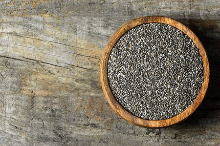 Chia seeds (Salvia Hispanica) in bowl on wooden rustic background. Cereal healthy food contains omega 3, a dietary supplement gluten free Imagens