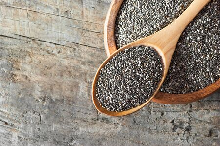 Chia seeds (Salvia Hispanica) in wooden spoon and bowl on wooden rustic background. Cereal healthy food contains omega 3, a dietary supplement gluten free