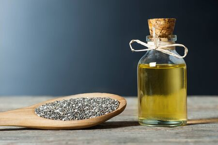 Glass bottle of Chia oil and Chia seeds (Salvia Hispanica) in wooden spoon on wooden rustic background