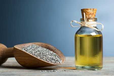 Glass bottle of Chia oil and Chia seeds (Salvia Hispanica) in wooden shovel on wooden rustic background Imagens