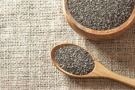 Chia seeds (Salvia Hispanica) in wooden spoon and bowl on burlap sack backdrop. Cereal healthy food contains omega 3, a dietary supplement gluten free