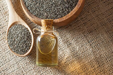 Glass bottle of chia oil and Chia seeds (Salvia Hispanica) in wooden spoon and bowl on burlap sack backdrop