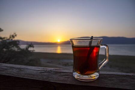 Glass cup of Turkish tea during sunset of Burdur lake in Turkey Фото со стока