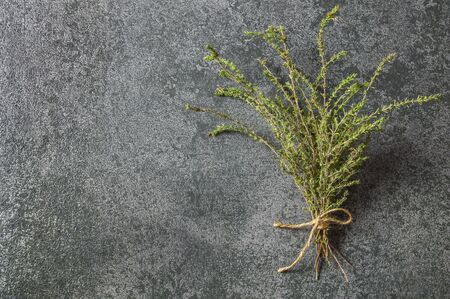 Top view bounded thyme bunch on gray rustic table. Healthy spice concept Banco de Imagens