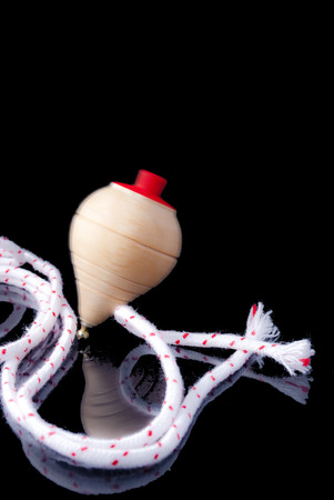 Classic spinning top game on black background photo