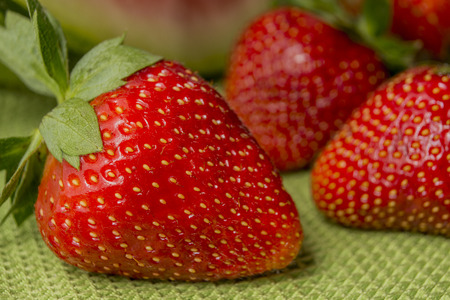 huelva: Red fruits  Three strawberries in Huelva on a green tablecloth  Background watermelon