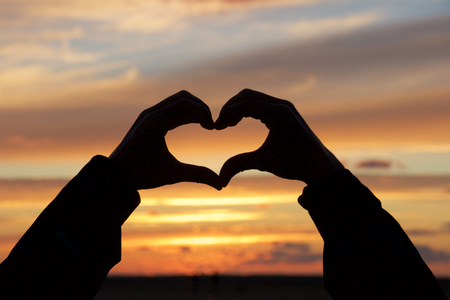 Hands forming the shape of a heart at sunset Stock Photo