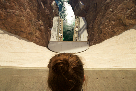 famous industries: Woman looking down Hoover Dam Stock Photo