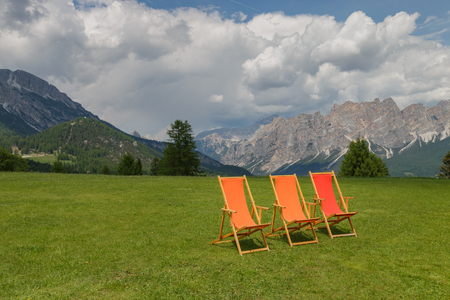 Orange and red deck chairs on a meadow in the Italian alps waiting for people to sit down