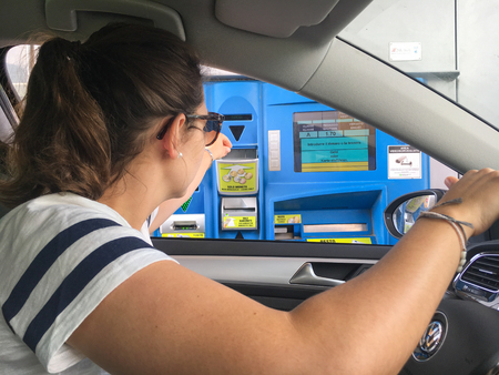 Vipiteno, Italy - June 1, 2017: Woman in a car paying cash at Italian tollbooth for using the highway