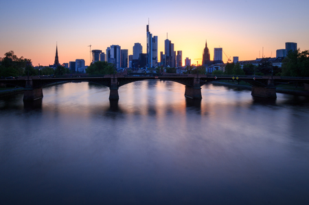 Cityscape with skyline of Frankfurt am Main seen from Floesserbruecke at sunset Stock Photo