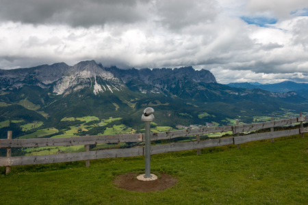 Panoramic view of Wilder Kaiser Mountains, Austria with a telescope infront of a wooden fence