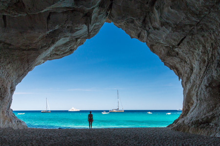 Woman inside a cave at Cala Luna beach on the Italian island of Sardinia