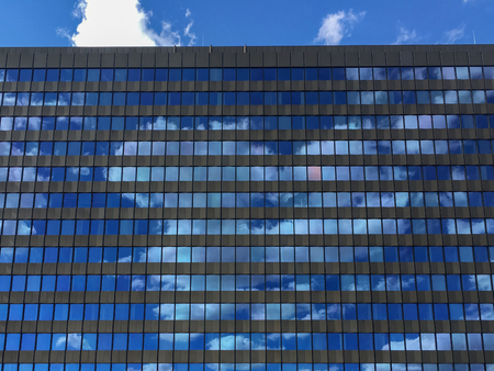 Office building windows with reflecting blue sky and clouds Imagens