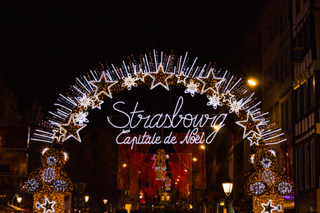 Illuminated arch saying Strasbourg the capital of Christmas at the entrance to Christmas market city center of Strasbourg