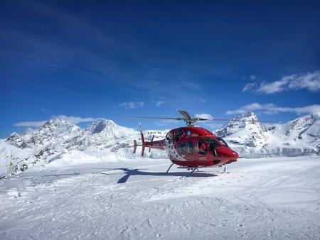 Zermatt, Switzerland - March 20, 2018: A red helicopter of Air Zermatt is waiting for takeoff from ski resort