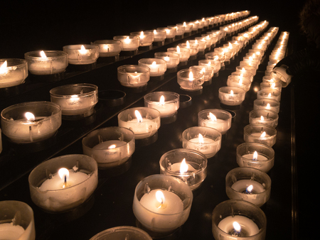 Votive candles or prayer candles in a church intended to be burnt as a votive offering in an act of Christian prayer