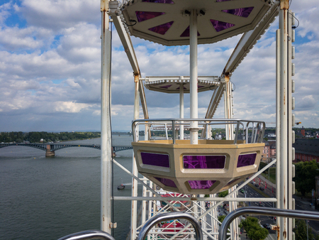 A Ferris wheel gondola with river Rhine and Theodor Heuss bridge in the background in Mainz, Germany during St. John's Night (Johannisnacht)
