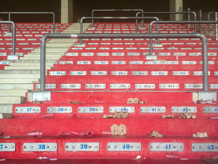 Empty red painted stand in a sports stadium with some rubbish after a match