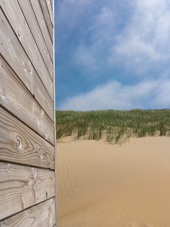 Summertime picture with gray patina wood in front of sand dunes and blue sky