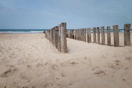 Beach poles wavebreaker on the beach of Domburg, Zeeland, the Netherlands Imagens
