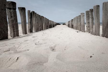Beach poles wavebreaker on the beach of Domburg, Zeeland, the Netherlands Stock Photo