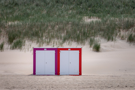 Two colorful beach cabins at North Sea beach of Domburg, Zeeland, the Netherlands in front of overgrown sand dunes Imagens