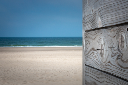 Summertime picture with gray patina wood in front of sandy beach and blue sky