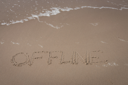 """The word """"offline"""" written in the sand on a beach with an upcoming wave symbolizing a time-out Imagens"""