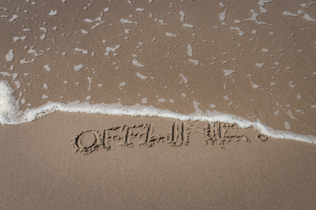 """The word """"offline"""" written in the sand on a beach partly washed away by a wave symbolizing a time-out Stock fotó"""