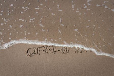 """The word """"offline"""" written in the sand on a beach partly washed away by a wave symbolizing a time-out Imagens"""