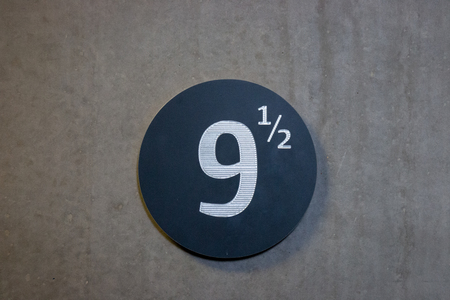 Silver colored number 9 ½ (9,5) on a black round background on a gray concrete wall