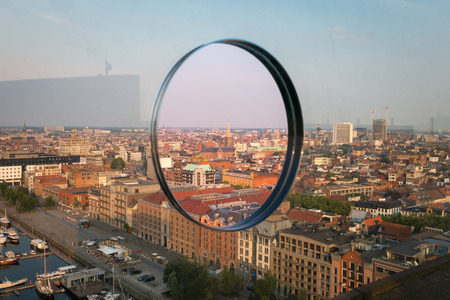 Cityscape of the Belgian city of Antwerp seen through a hole in a glass