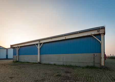 Exterior picture of a blue and old storage hall in an industrial area Imagens