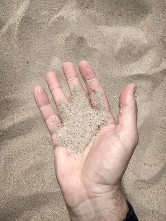 Man having sand in his open hand