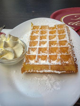 Famous Belgian waffle with cream on powder sugar