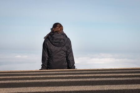 Woman sitting on a crosswalk above the clouds at Haleakala National Park on the Hawaiian Island of Maui, USA