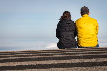 Couple sitting on a crosswalk above the clouds at Haleakala National Park on the Hawaiian Island of Maui, USA Imagens
