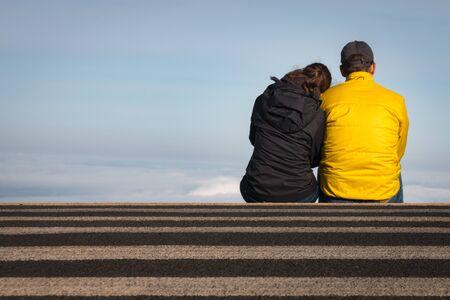 Couple sitting on a crosswalk above the clouds at Haleakala National Park on the Hawaiian Island of Maui, USA Archivio Fotografico - 125515751