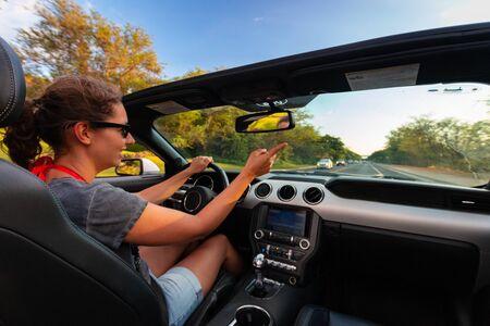 Kihei, HI, USA - 10 november 2016: Lachende vrouw met zonnebril geniet van het besturen van een cabriolet
