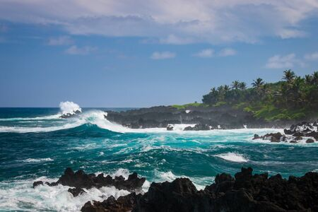 Rough black coastline at Waianapanapa State Park on the Hawaiian island of Maui along Road to Hana, USA