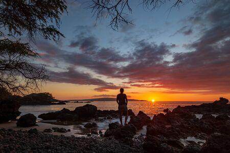 Woman watching sunset at Makena Bay on the Hawaiian island of Maui