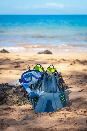 Snorkeling equipment consisting of snorkel, diving goggles and flippers Snorkeling equipment lying on a beach Imagens - 125515948