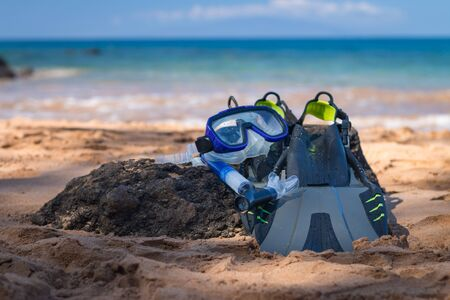 Snorkeling equipment consisting of snorkel, diving goggles and flippers Snorkeling equipment lying on a beach Imagens - 125515950