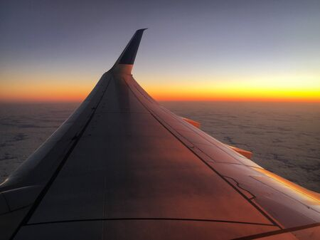 Aerial of right airplane wing at sunset above the clouds Imagens