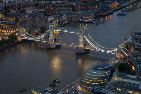 Aerial cityscape of London at night with urban architectures and Tower Bridge, United Kingdom