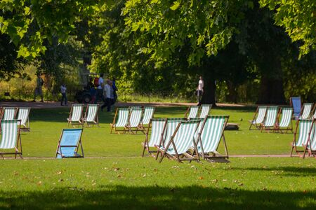 Comfortable deck chair inviting people to relax on summer day in beautiful St. James park, London, UK Imagens - 131942947